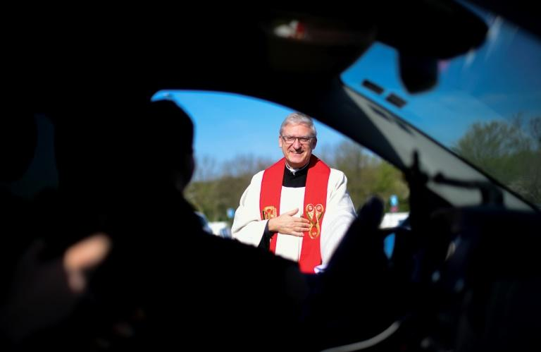 Pastor Frank Heidkamp talks to a worshipper behind the wheel during an Easter 'drive-in' service on a giant car park