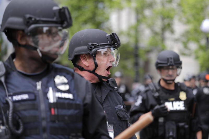 FILE - In this June 3, 2020, file photo, a Seattle police officer yells out orders at Seattle City Hall as protesters march toward them, in Seattle, following protests over the death of George Floyd, a black man who was in police custody in Minneapolis. The King County Labor Council, the largest labor group in the Seattle area, vote Wednesday night June 17 to expell the city's police union, saying the guild representing officers failed to address racism within its ranks. (AP Photo/Elaine Thompson, File)