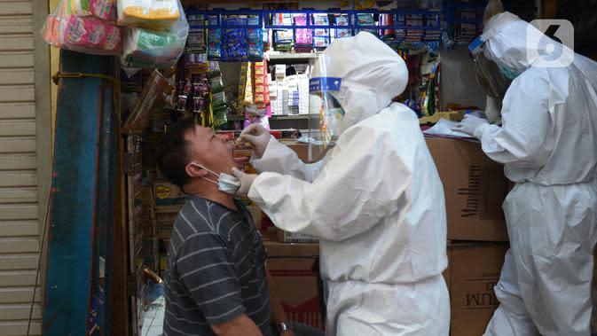 Petugas medis melakukan tes usap (swab test) ke pedagang Pasar Karang Anyar di Jakarta, Kamis (26/6/2020). Tes swab dengan metode PCR dilakukan secara masif setelah adanya pelonggaran PSBB, terutama di wilayah yang berpotensi tinggi menjadi tempat penularan Covid-19. (merdeka.com/Imam Buhori)