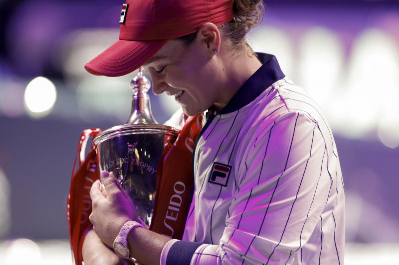 Ashleigh Barty of Australia holds her winning trophy on stage after defeating Elina Svitolina of Ukraine in the WTA Finals Tennis Tournament at the Shenzhen Bay Sports Center in Shenzhen, China's Guangdong province, Sunday, Nov. 3, 2019. (AP Photo/Andy Wong)