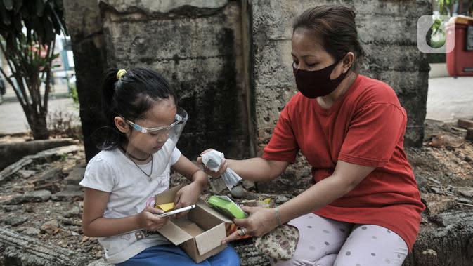 Seorang anak didampingi orang tua saat membuka boks donasi ponsel saat acara #PonselPintarUntukPelajar di Jakarta, Minggu (9/8/2020). Donasi diharapkan dapat membantu mereka dalam mengikuti kegiatan Pelajaran Jarak Jauh (PJJ). (merdeka.com/Iqbal S. Nugroho)