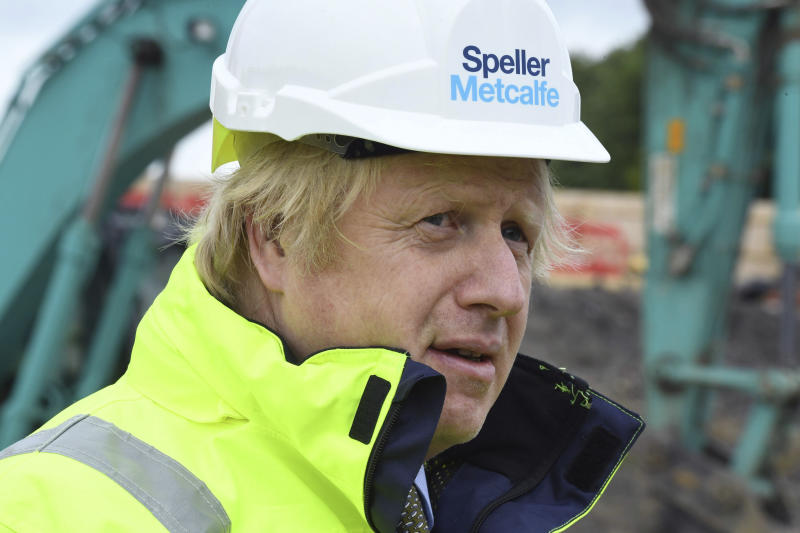 """Britain's Prime Minister Boris Johnson looks on during a visit to the Speller Metcalfe's building site at the Dudley Institute of Technology, in Dudley, England, Tuesday, June 30, 2020.  Johnson is expected to announce a multi-billion pound """"new deal"""" for infrastructure projects to help stimulate the nation's recovery from the coronavirus pandemic. (Jeremy Selwyn/Pool Photo via AP)"""