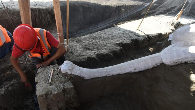Ahli paleontologi dari Institut Antropologi Nasional bekerja menggali kerangka mammoth yang ditemukan di Pangkalan Militer Santa Lucia di Kotamadya Zumpango, Meksiko (8/9/2020). Setidaknya ada sekitar 200 fosil ditemukan di lokasi tersebut. (AFP/Rodrigo Arangua)