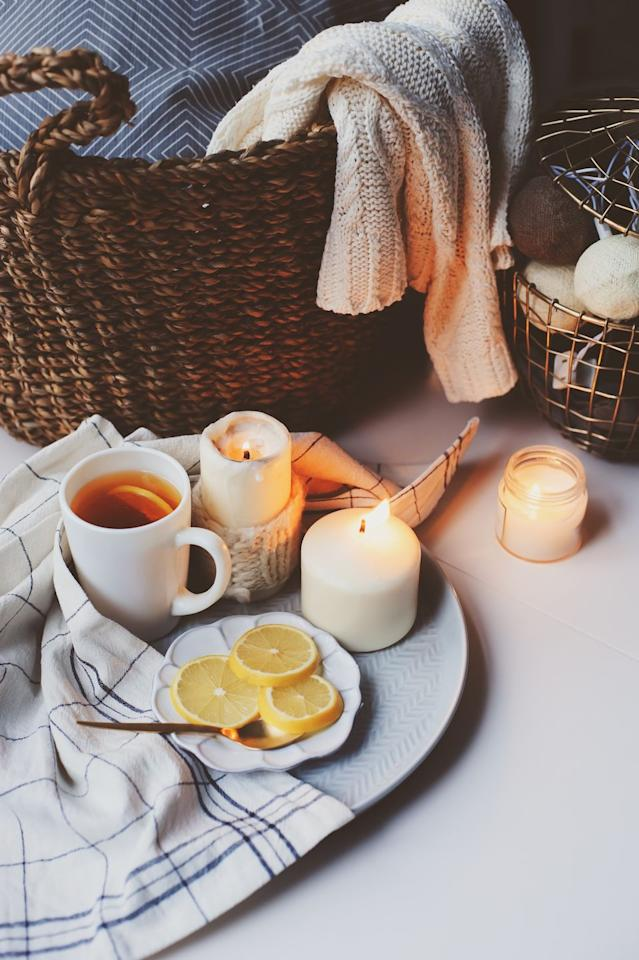 """<p>Few things feel more inviting than the <a href=""""https://www.harlemcandlecompany.com/"""" target=""""_blank"""">soft glow of a candle</a> flickering in the corner of a room, especially if it gives off a delicious scent. These are so easy and inexpensive to add for ambiance that it's almost silly not to try. """"Scent is a major element that is often overlooked, and the right scent can immediately make you feel calmer and more relaxed,"""" says Nicole Gibbons, interior designer and founder of <a href=""""http://www.clare.com/"""">Clare</a>. </p><p>You should also play around with varying sizes and shapes of candles instead of just placing one on a space. """"Find a larger candle and add it to a coffee table or side table,"""" says Mollee Johnson, interior designer and owner of <a href=""""https://style1519.com/"""" target=""""_blank"""">Style 1519.</a>  Place that larger candle next to two smaller ones if you want to create a cozy nook. </p>"""