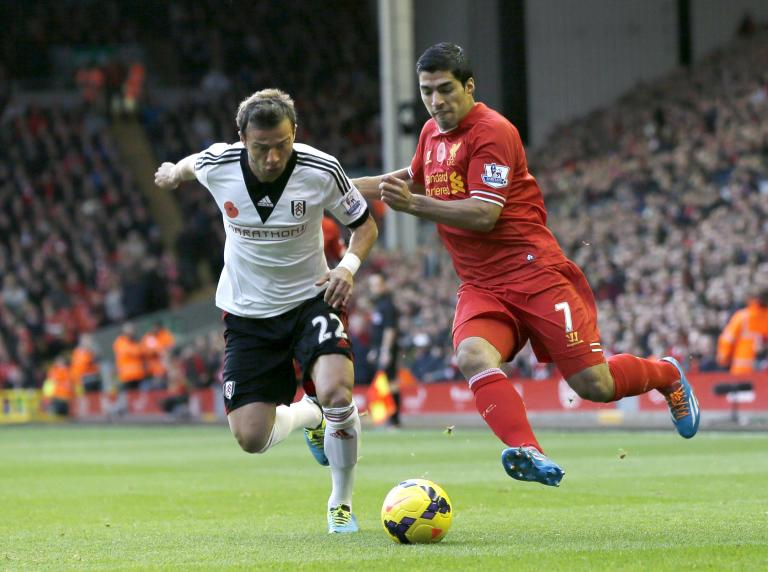 Liverpool's Suarez challenges Fulham's Zverotic during their English Premier League soccer match at Anfield in Liverpool