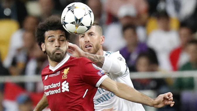 Striker Liverpool, Mohamed Salah, berebut bola dengan bek Real Madrid, Sergio Ramos, pada laga final Liga Champions di Stadion NSC Olimpiyskiy, Kiev, Minggu (27/5/2018). Salah mengalami cedera bahu usai dilanggar Ramos. (AP/Efrem Lukatsky)