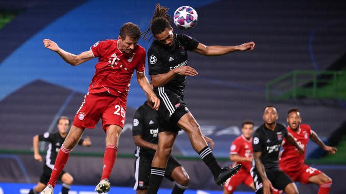 Penyerang Bayern Munchen, Thomas Mueller (kiri) berebut bola udara dengan bek Lyon, Jason Denayer pada pertandingan Semifinal Liga Champions di stadion Jose Alvalade di Lisbon, Portugal, Rabu, (19/8/2020). Munchen menang telak 3-0 dan melaju ke Final. (Franck Fife / Pool via AP)