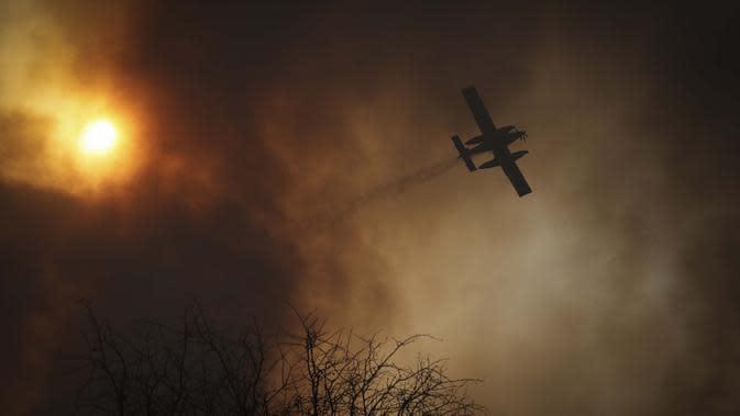 Sebuah pesawat menjatuhkan air saat terjadi kebakaran di Cordoba, Argentina, Senin (12/10/2020). Kebakaran hutan telah menghancurkan ribuan hektare di Provinsi Cordoba tahun ini, di tengah kekeringan dan suhu tinggi. (AP Photo/Nicolas Aguilera)