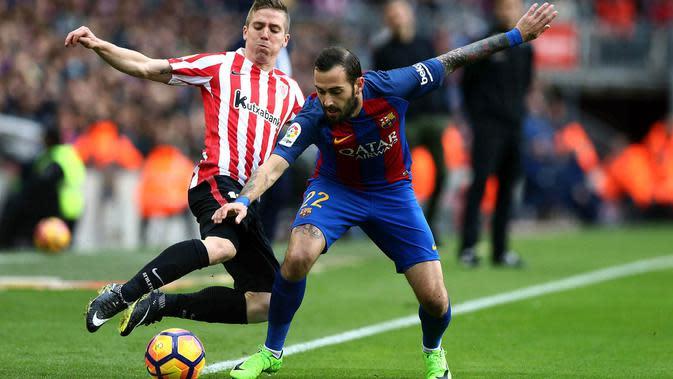 Gelandang Barcelona, Aleix Vidal, menghadang striker Athletic Bilbao, Iker Muniain. Kemenangan ini memantapkan posisi Barcelona di peringkat kedua klasemen Liga Spanyol menempel Real Madrid. (EPA/Toni Albir)