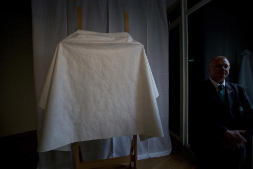 A security guard stands next to a covered easel prior to a press conference at the Van Gogh Museum in Amsterdam, Netherlands, Monday Sept. 9, 2013. The museum announced it has made an significant new discovery related to the famous Dutch master. (AP Photo/Peter Dejong)