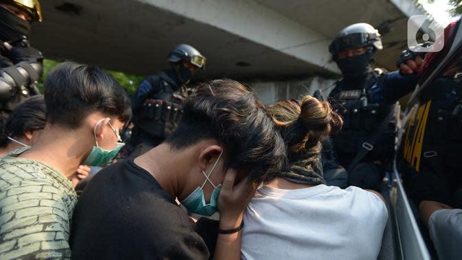 Polisi membawa pelajar yang terjaring razia saat berkumpul di sekitar Gedung DPR/MPR, Jalan Gatot Subroto, Jakarta, Rabu (7/10/2020). Sejumlah akses jalan menuju lokasi dijaga menyusul adanya aksi demonstrasi kelompok buruh yang menolak UU Omnibus Law Cipta Kerja. (merdeka.com/Imam Buhori)