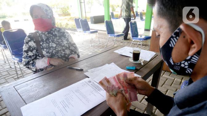 Petugas sedang menyerahkan Bantuan Langsung Tunai Dana Desa (BLT-DD) kepada warga Desa Curug di Kantor Desa Curug, Gunung Sindur, Kabupaten Bogor, Jawa Barat, Kamis (17/09/2020). (merdeka.com/Dwi Narwoko)