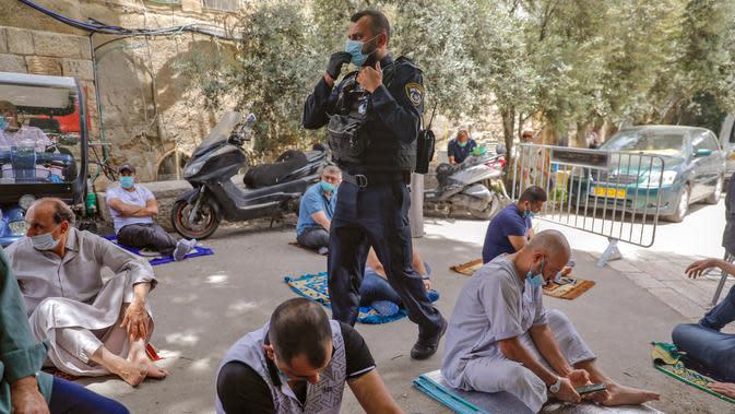 Anggota pasukan keamanan Israel berjaga saat seorang jemaah Palestina menghadiri salat Jumat selama bulan suci Ramadan di tengah krisis pandemi coronavirus di luar kompleks masjid al-Aqsa di Kota Tua Yerusalem (15/5/2020). (AFP/Ahmad Gharabli)