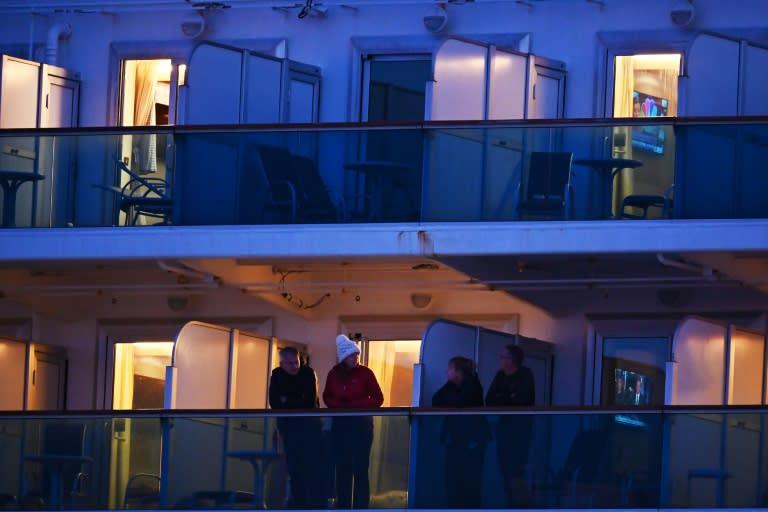 Diamond Princess passengers stand on the cruise ship's balconies on February 18, 2020