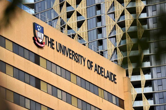 A building with a University of Adelaide sign on it with a taller one in the background