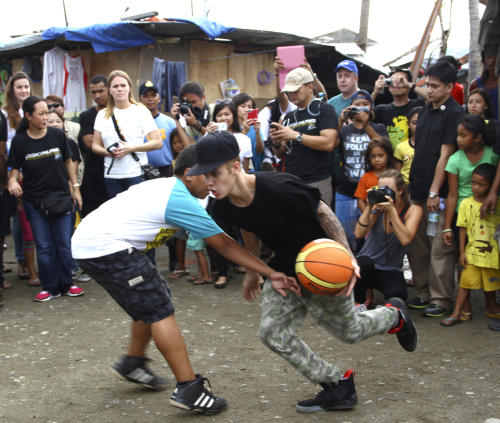 Justin Bieber plays basketball with children survivors of typhoon Haiyan during his visit Tuesday, Dec. 10, 2013 at Tacloban city, Leyte province in central Philippines. The teen heartthrob Bieber arrived Tuesday in the Philippines, where he has launched a campaign to help victims of last month's killer typhoon. (AP Photo)