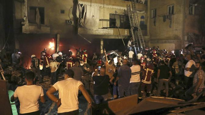 Petugas pemadam kebakaran memadamkan api di gedung setelah tangki bahan bakar meledak di lingkungan Tariq al-Jdide di Beirut (9/10/2020). Dilansir dari AP pada Sabtu (10/10/2020) sejauh ini belum ada pengumuman mengenai penyebab pasti kebakaran tangki yang memicu ledakan. (AP Photo/Bilal Hussein)