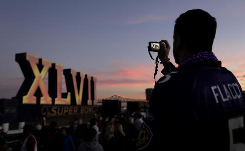 Greg Fox, from Baltimore, Md., photographs the Roman numerals for NFL Super Bowl XLVII as they they float on the Mississippi River Saturday, Feb. 2, 2013, in New Orleans. The city will host the football game between the San Francisco 49ers and Baltimore Ravens on Sunday. (AP Photo/Charlie Riedel)