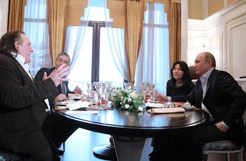 French actor Gerard Depardieu, left, speaks to President Vladimir Putin and unidentified aides after his arrival late Saturday, Jan. 5, 2013, at the president's residence in Sochi, the host city of the 2014 Winter Olympics. Depardieu has received a Russian passport after flying to Russia for a late night dinner with President Vladimir Putin. Depardieu sought Russian citizenship as part of his battle against a proposed super tax on millionaires in France, and Putin granted his request last week. (AP Photo/RIA-Novosti, Mikhail Klimentyev, Presidential Press Service)