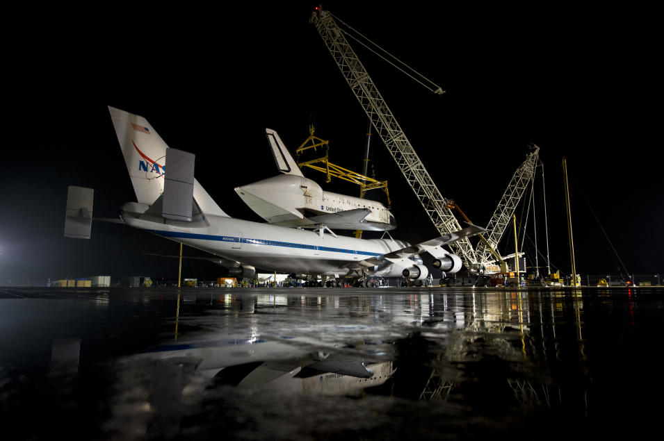 In this image provided by NASA the NASA 747 Shuttle Carrier Aircraft with the space shuttle Discovery mated on top rolls into position for demating at Washington Dulles International Airport, Wednesday, April 17, 2012, in Sterling, VA.  Discovery, the first orbiter retired from NASA's shuttle fleet, completed 39 missions, spent 365 days in space, orbited the Earth 5,830 times, and traveled 148,221,675 miles. NASA will transfer Discovery to the National Air and Space Museum to begin its new mission to commemorate past achievements in space and to educate and inspire future generations of explorers. (AP Photo/NASA, Bill Ingalls)