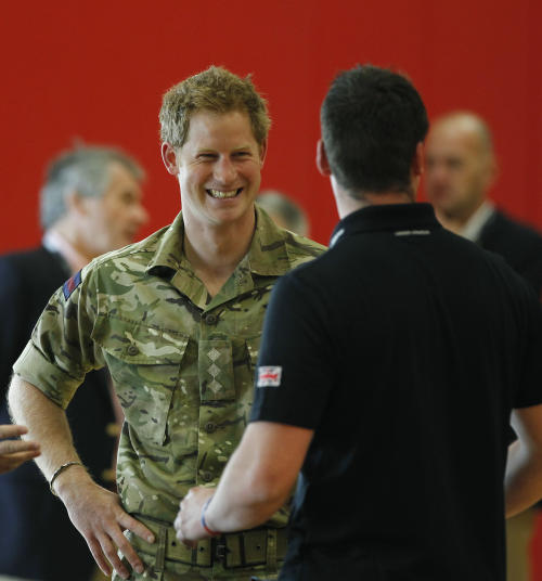 Britain's Prince Harry talks with members of the British Warrior Games Team who relaxed in a gymnasium before the opening of the 2013 Warrior Games, at the U.S. Olympic Training Center, in Colorado Springs, Colo., Saturday May 11, 2013. (AP Photo/Brennan Linsley, Pool)
