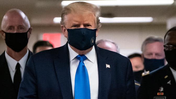 Presiden Amerika Serikat Donald Trump mengenakan masker saat mengunjungi Pusat Kesehatan Militer Nasional Walter Reed di Bethesda, Maryland, Sabtu (11/7/2020). Donald Trump akhirnya menggunakan masker untuk pertama kalinya di depan umum sejak pandemi COVID-19 melanda negara itu. (ALEX EDELMAN/AFP)