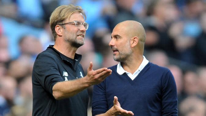 Pelatih Liverpool Juergen Klopp (kiri) dan pelatih Manchester City Pep Guardiola berdebat saat menyaksikan pertandingan Manchester City menjamu Liverpool di Stadion Etihad, Manchester (9/9). (AP Photo/Rui Vieira)