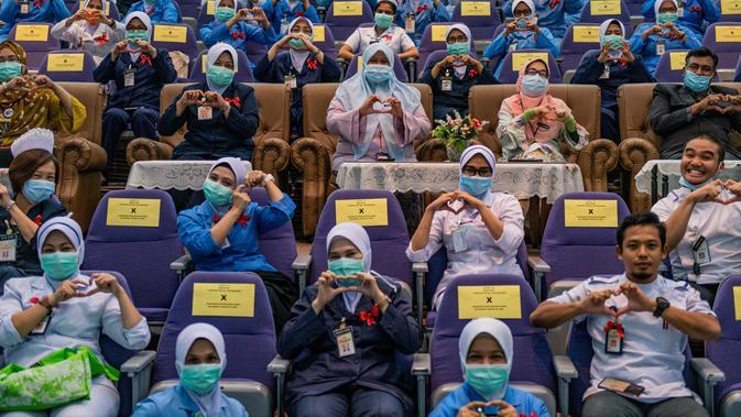 Para perawat membuat simbol cinta saat peringatan Hari Perawat Internasional di Rumah Sakit Selayang, Selayang, Malaysia, Selasa (12/5/2020). Hari Perawat Internasional tahun ini diperingati di tengah pandemi virus corona COVID-19. (Mohd RASFAN/AFP)