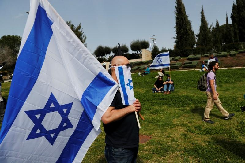 Israelis hold national flags during a demonstration against PM Netanyahu's caretaker government, in Jerusalem