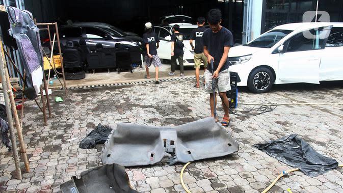 Pekerja mencuci bagian mobil yang terkena banjir di bengkel Detailing, Shop, Garage (DSG) di kawasan Pondok Pinang, Jakarta, Kamis (9/1/2020). Biaya yang harus dikeluarkan pemilik mobil berkisar Rp 2 juta hingga Rp 6 juta tergantung tingkat kerusakan kendaraan. (merdeka.com/Arie Basuki)