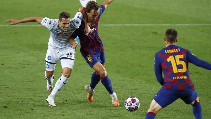 Penyerang Napoli, Arkadiusz Milik berebut bola dengan gelandang Barcelona, Ivan Rakitic pada leg kedua babak 16 besar Liga Champions di Stadion Camp Nou , Spanyol, Sabtu (8/82020). Barcelona menang 3-1 atas Napoli dan melaju ke perempat final dengan agregat skor 4-1. (AP Photo/Joan Monfort)