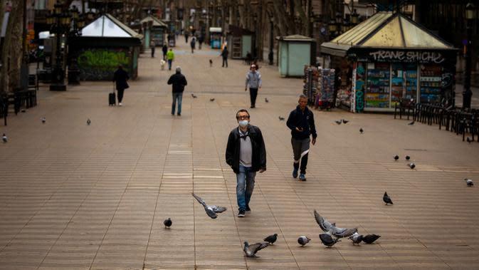 Warga berjalan di sepanjang La Ramblas, Barcelona, Spanyol, Minggu (15/3/2020). Pemerintah Spanyol memberlakukan lockdown setelah negara berpenduduk 47 juta jiwa itu terdampak virus corona COVID-19 paling parah kedua di Eropa setelah Italia. (AP Photo/Emilio Morenatti)