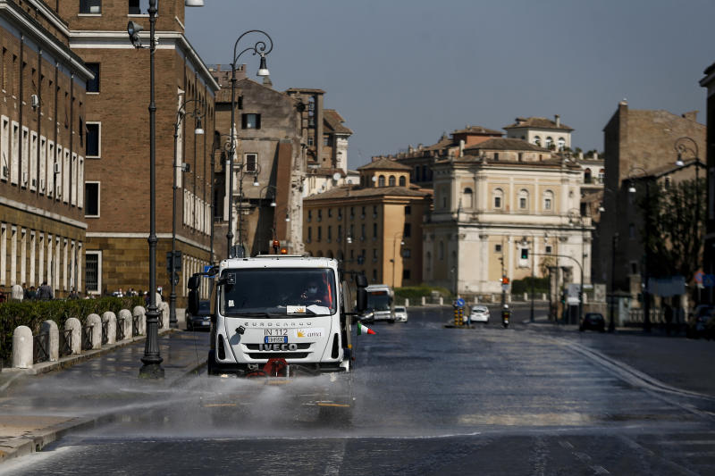 A street cleaner truck sprays disinfectant on a street to avoid the spread of Covid-19 virus, in central Rome, Wednesday, April 8, 2020. The new coronavirus causes mild or moderate symptoms for most people, but for some, especially older adults and people with existing health problems, it can cause more severe illness or death. (Cecilia Fabiano/LaPresse via AP)