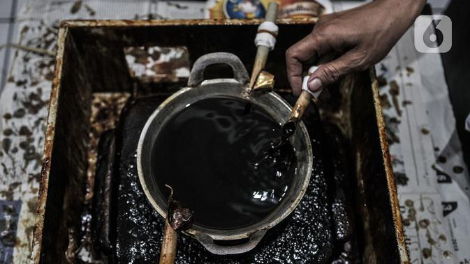 Perajin menyelesaikan pembuatan batik edisi Jakarta Terkini di Rumah Batik Palbatu, Kamis (15/10/2020). Kain batik Jakarta Terkini bergambar virus Covid-19 dipadukan ikon-ikon Ibu Kota seperti Monas, Tanjidor, dan ondel-ondel dibanderol Rp250 ribu - Rp350 ribu per buah. (merdeka.com/Iqbal Nugroho)