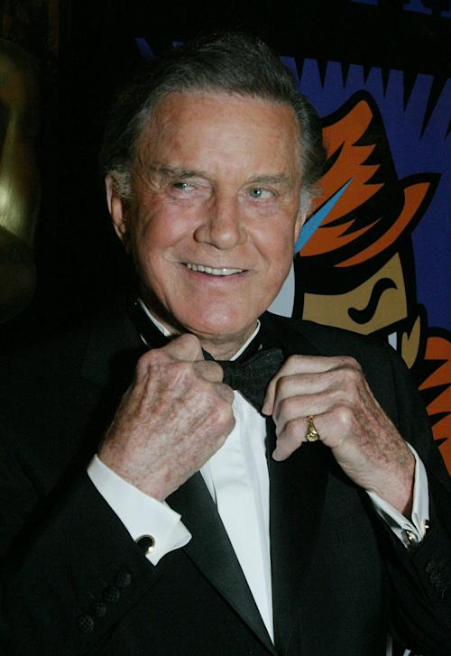 """FILE - In this Feb. 29, 2004 file photo, actor, writer, director and producer Cliff Robertson straightens his tie as he arrives for the Academy of Motion Picture Arts and Sciences' official New York Oscar Night celebration of the 76th Academy Awards in New York. Robertson, played John F. Kennedy in """"PT-109,"""" won an Oscar for """"Charly"""" and was famously victimized in a 1977 Hollywood forgery scandal, died Saturday. He was 88. (AP Photo/Tina Fineberg, File)"""