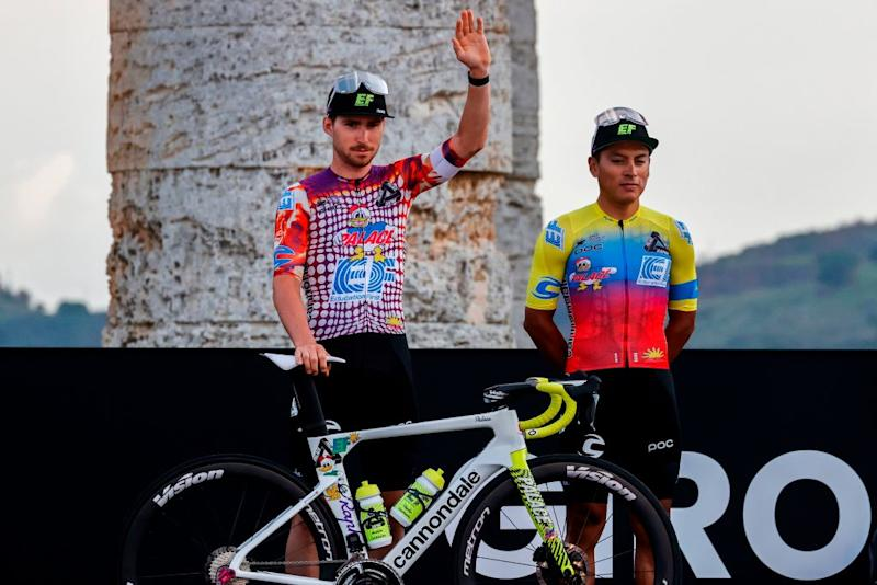 Team Education First rider US Sean Bennett L waves on stage at the Doric Temple of Segesta near Palermo Sicily on October 1 2020 during an opening ceremony of presentation of participating teams and riders two days ahead of the departure of the Giro dItalia 2020 cycling race Photo by Luca Bettini AFP Photo by LUCA BETTINIAFP via Getty Images