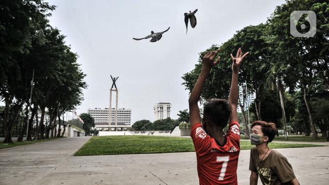 Anak-anak bermain burung dara di depan Lapangan Banteng, Jakarta, Kamis (15/9/2020). Lapangan Banteng dan hutan kota di Ibu Kota Kembali ditutup sementara saat penerapan pembatasan sosial berskala besar (PSBB) Jakarta guna menekan penyebaran Covid-19 di ruang publik. (merdeka.com/Iqbal Nugroho)