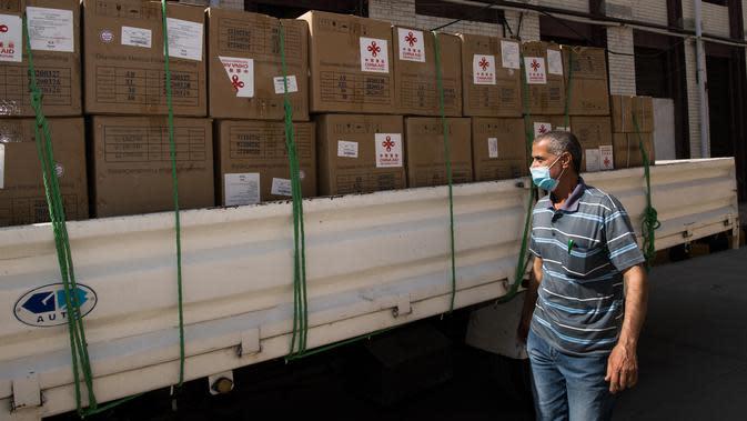 Seorang pekerja berdiri di depan pasokan medis sumbangan dari China terlihat di Kairo, Mesir (10/5/2020). Mesir pada Minggu (10/5) menerima kelompok pengiriman bantuan medis kedua dari pemerintah China bagi negara di kawasan Afrika Utara tersebut untuk memerangi wabah Covid-19. (Xinhua/Wu Huiwo)