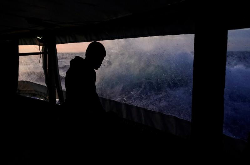 A migrant looks at waves on board of NGO Proactiva Open Arms rescue boat in central Mediterranean Sea