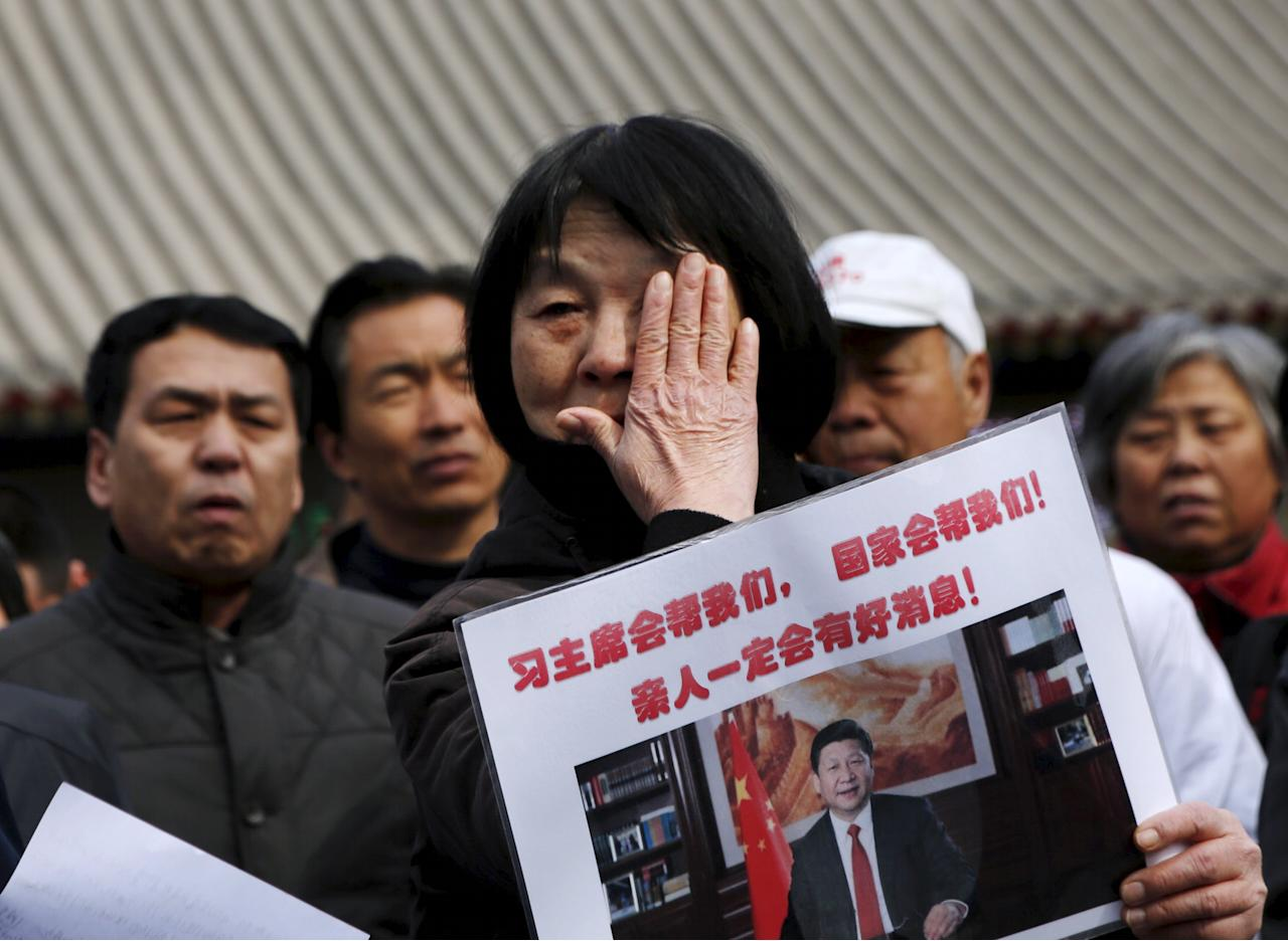 """Dai Shuqin, whose family members were onboard Malaysia Airlines flight MH370 which went missing in 2014, wipes away tears as she holds a placard with Chairman Xi's photo on it, in front of a holding area for journalists at Lama Temple in Beijing, China, March 8, 2016. The Chinese characters on the placard reads """"Chairman Xi will help us. Our country will help us. Loved ones will definitely have good news."""" REUTERS/Kim Kyung-hoon"""