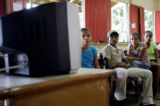"""Students watch a video during a """"tele-learning"""" class in Xapuri, in northern Brazil. Teachers, who are scarce in the Amazon, are now conducting lessons streamed to students in the village of Tumbira using an Internet connection made possible with a generator-powered radio signal"""