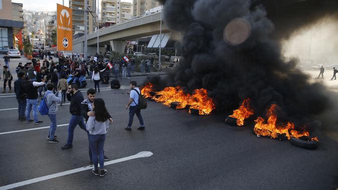 Demonstran antipemerintah membakar ban saat protes menentang elite penguasa di Kota Jal el-Dib, Lebanon, Selasa (14/1/2020). Demonstran menganggap elite penguasa gagal mengatasi ekonomi yang menurun tajam. (AP Photo/Bilal Hussein)