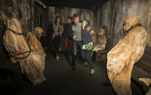 """This Friday, Sept. 20, 2013 publicity photo released by Universal Studios Hollywood captures guests experiencing the """"Insidious: Into the Further"""" maze based on the recent blockbuster film """"Insidious: Chapter 2"""" during Halloween Horror Nights in Universal City, Calif. Several spooks at this year's Halloween Horror Nights are hyping new releases from the entertainment industry. Besides """"13"""" from Sabbath, there's a """"scare zone"""" populated by actors dressed as the nasty Chucky doll from the direct-to-DVD sequel """"Curse of Chucky,"""" and a new maze incorporating supernatural elements from the """"Insidious"""" films. (AP Photo/Universal Studios Hollywood)"""