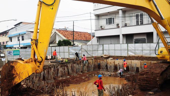 Pekerja menyelesaikan proyek tahap awal galian sodetan Kali Ciliwung di kawasan Otista, Jakarta, Kamis (10/7/14). (Liputan6.com/Faizal Fanani)