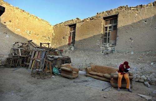 In this photo taken in Saturday, May 19, 2012, an Egyptian woman sits on a couch in the graveyard where she lives in a necropolis called the City of the Dead, in Cairo, Egypt. The City of the Dead is a 4 mile (6.4 kilometer) long necropolis where thousands of Egyptians are forced to live and work alongside graves due to the scarcity of housing in the capital. (AP Photo/Khalil Hamra)