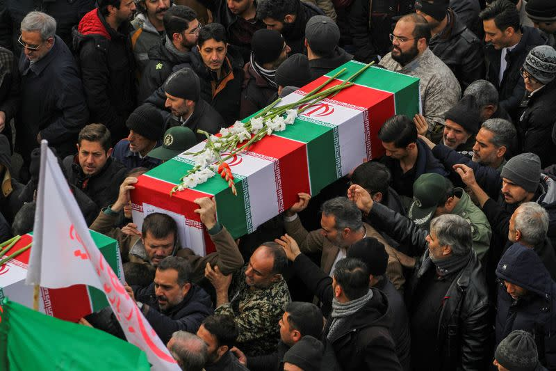 FILE PHOTO: Iranian people carry coffins during the funeral procession and burial of four Iranian victims of the Ukrainian plane crash in Iran, in Hamadan