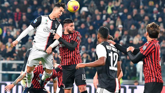 Penyerang Juventus, Cristiano Ronaldo melompat saat berebut bola dengan pemain AC Milan Hernandez Theo pada pekan 12 Liga Italia 2019-2020 di Allianz Stadium, Minggu (10/11/2019). Juventus semakin kokoh di puncak klasemen Liga Italia usai menundukkan AC Milan 1-0. (Alessandro Di Marco/ ANSA via AP)