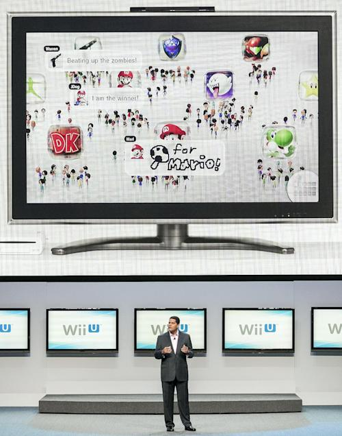 "FILE - In this June 5, 2012 file photo, Reggie Fils-Aime, president and CEO of Nintendo America, Inc., presents the Wii U as the next-generation game console at the Nintendo All-Access presentation at E3 2012 in Los Angeles. It can scan zombies, replace a TV remote, open a window into virtual worlds and shoot ninja stars across a living room. It's the Wii U GamePad, the 10-by-5-inch touchscreen controller for the successor to the Wii out Sunday, Nov. 18, 2012, and if you ask the brains behind the ""Super Mario Bros."" about it, they say it's going to change the way video games are made and played. (AP Photo/Damian Dovarganes, File)"