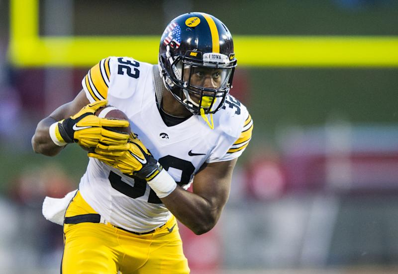 Iowa running back Derrick Mitchell Jr. (32) rushes the ball into the Indiana defense during the second half of an NCAA college football game in Bloomington, Ind., Saturday, Nov. 7, 2015. Iowa won 35-27. (AP Photo/Doug McSchooler)