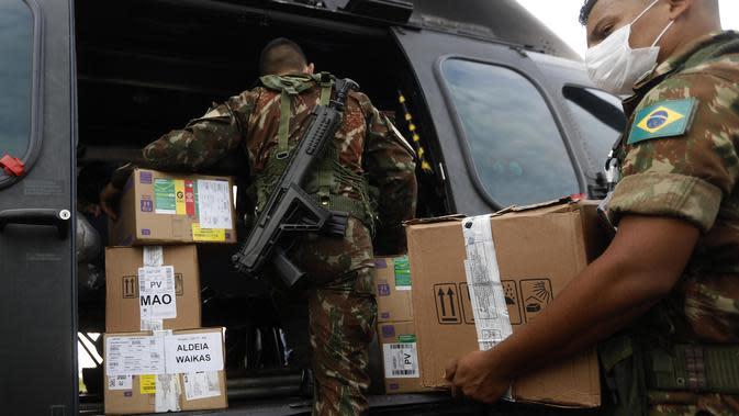 Personel militer mengangkut pasokan medis ke dalam helikopter yang akan menjangkau masyarakat pribumi di Boa Vista, ibu kota Negara Bagian Roraima, Brasil (30/6/2020). (Xinhua/Lucio Tavora)